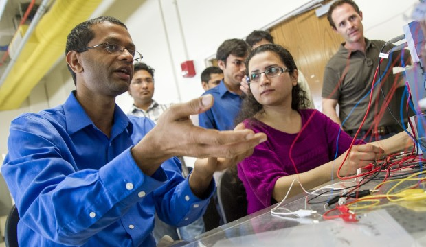 Mechanical and aeronautics engineering Professor Ankur Jain with students looking at a computer screen.