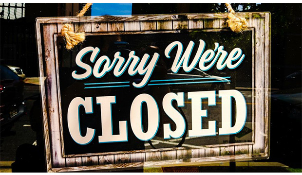 """Sign on door with """"Sorry, We're Closed"""""""