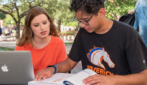 Two students look at a laptop computer.