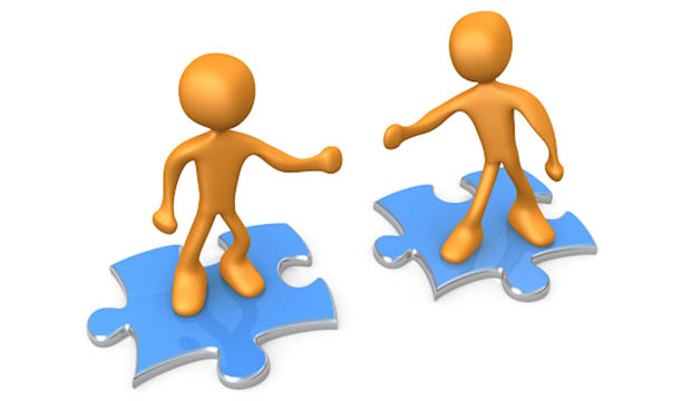 Two minions standing on jigsaw puzzles, reaching out to each other