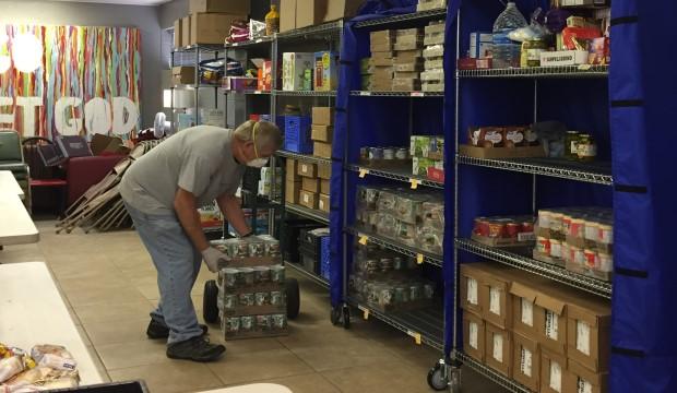 TIAA worker stocks shelves at UTA/Tri-C Food Pantry.