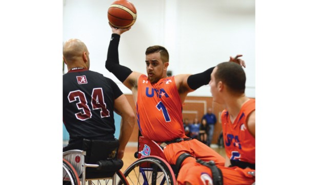 Movin' Mav wheelchair basketball player with ball surrounded by opposing team.