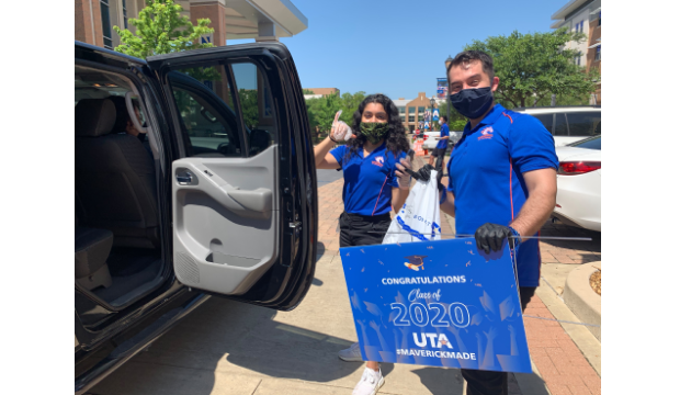 Two UTA employees with welcome signs beside a car at the drive-thru signing day for high school seniors.