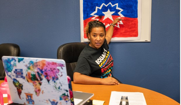 Melanie Johnson, Multicultural Affairs director, with a painting of the Juneteenth flag.