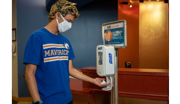 Student wearing a face mask put hand under hand sanitizer dispenser.