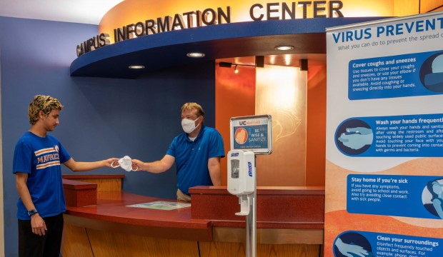 Man at University Center Information Center handing a face mask to a student.