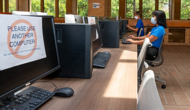 """Masked students in computer lab with sign on two computers between then that says """"Do Not Use This Computer."""""""