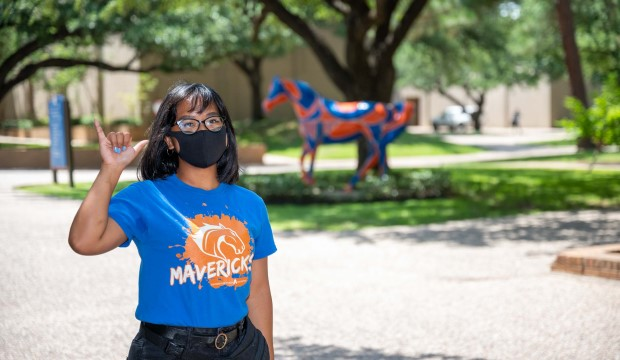 Masked female student stands in front of a painted Maverick horse.