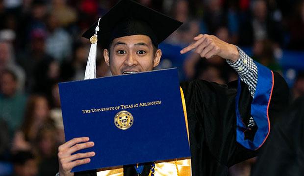 Graduate pointing at his new diploma.
