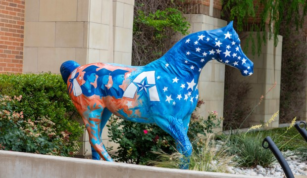 UTA painted horse with image of grads in mortarboards on it.