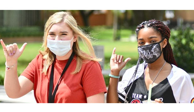 Two female students wearing masks showing the Maverick hand sign.