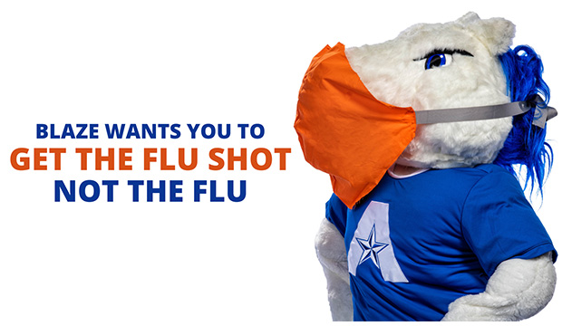 "Blaze, UTA mascot, wearing a mask, with ""Get The Flu Shot, Not The Flu."""