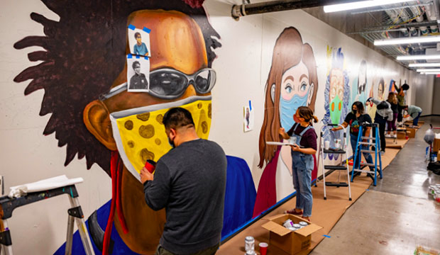 Artists painting mural of people wearing face masks.