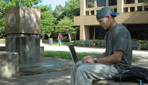 Student uses a laptop near the University Center.