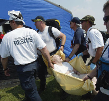 rescue squad carries a woman to a medical tent