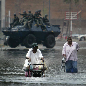 Louis Jones and Catherine McZeal wading through flooded street