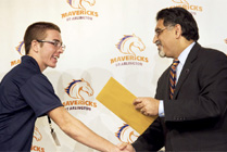 President Vistasp Karbhari shakes the hand of an Arlington high school student