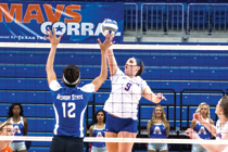 UTA volleyball player spikes the ball